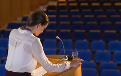 Side view of blonde Caucasian businesswoman looking in script  and trying to speak in the empty auditorium