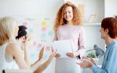 Jolly confident attractive young female marketing expert with red curly hair standing in front of applauding students and holding lecture using own notes in meeting room